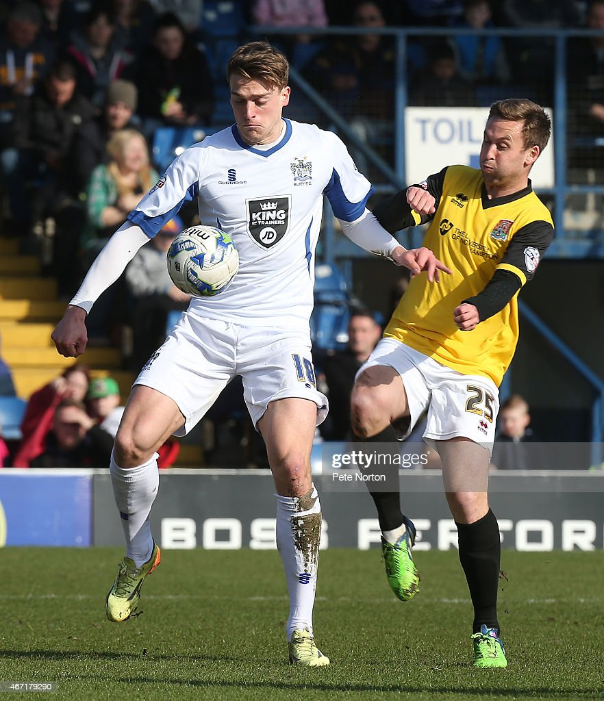 Tom Eaves of Bury looks to control the ball under pressure from Joel Byrom of Northampton Town during the Sky Bet League Two match between Bury and...