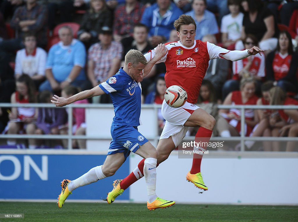 Tom Eaves of Rotherham United tackled by Craig Alcock of Peterborough United during the Sky Bet League One match between Rotherham United and Peterborough United at The New York Stadium on September 28, 2013 in Rotherham, England.