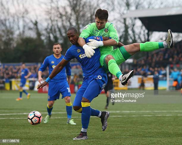 Tom Elliott of AFC Wimbledon and Ross Worner of Sutton United clash during The Emirates FA Cup Third Round match between Sutton United and AFC...
