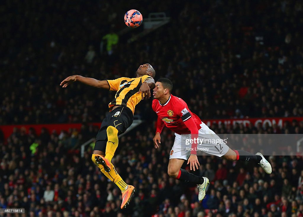 Tom Elliott of Cambridge United and Chris Smalling of Manchester United compete for the header during the FA Cup Fourth round replay match between Manchester United and Cambridge United at Old Trafford on February 3, 2015 in Manchester, England.