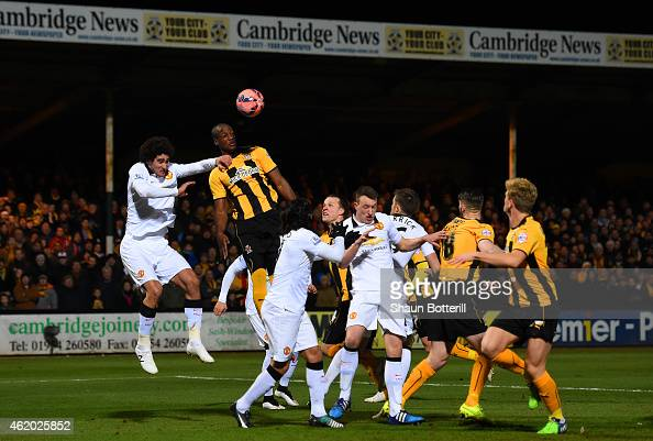 Tom Elliott of Cambridge United heads towards goal under pressure from Marouane Fellaini of Manchester United during the FA Cup Fourth Round match...