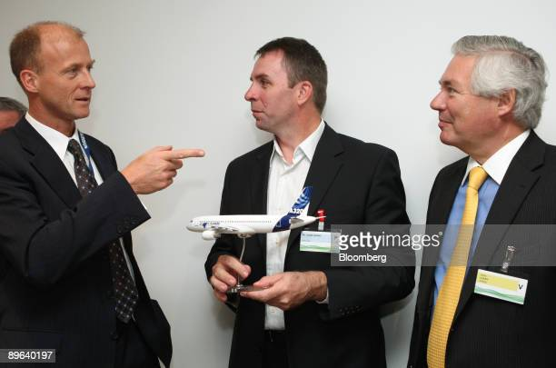 Tom Enders chief executive officer of Airbus SAS left speaks to Jozsef Varadi chief executive officer of Wizz Air Ltd as John Leahy chief commercial...