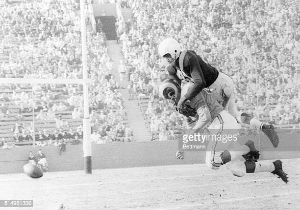 Tom Fears of the Los Angeles Rams drops an incompleted pass a split second before he was dropped himself by the weight of 'Night Train' Lane of the...