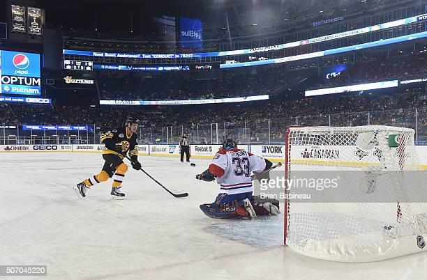Tom Fergus of the Boston Bruins Alumni Team shoots against goaltender Richard Sevigny of the Montreal Canadiens Alumni Team during shootout in the...