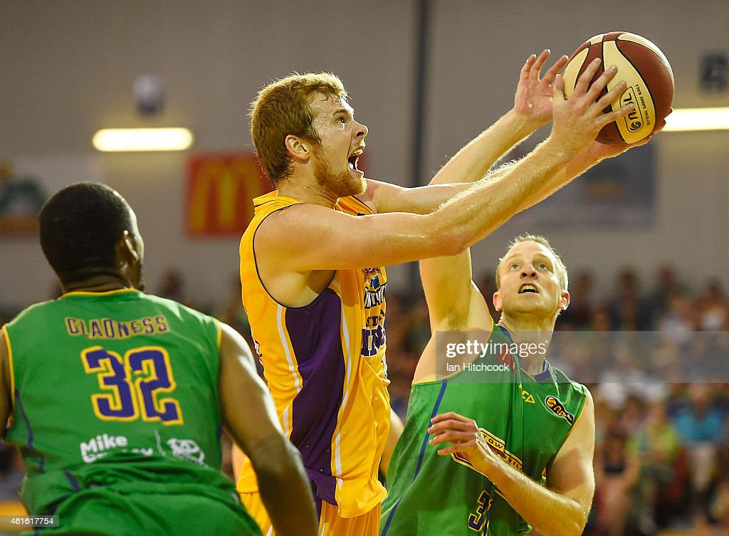 Tom Garlepp of the Kings attempts a layup past Jacob Holmes and Mickell Gladness of the Crocodiles during the round 15 NBL match between the Townsville Crocodiles and Sydney Kings at Townsville RSL Stadium on January 16, 2015 in Townsville, Australia.