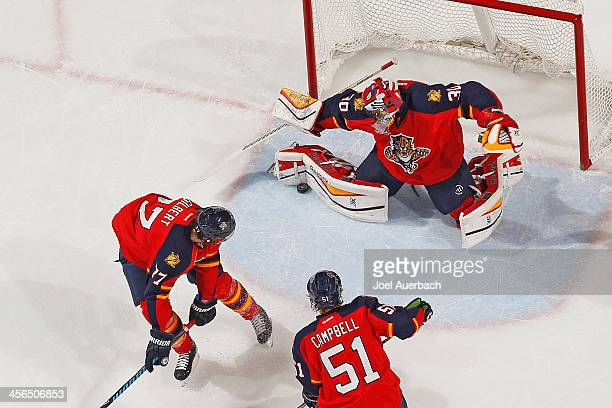 Tom Gilbert and Brian Campbell look on as goaltender Scott Clemmensen of the Florida Panthers makes a pad save against the Washington Capitals at the...