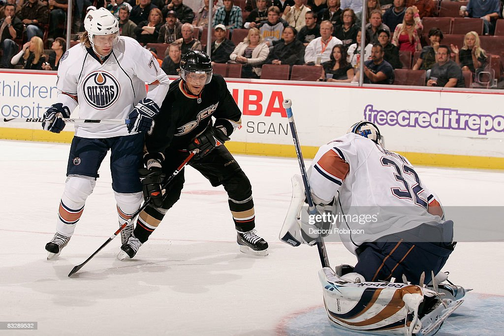 Tom Gilbert and Mathieu Garon of the Edmonton Oilers defend as Teemu Selanne of the Anaheim Ducks makes a shot on goal during the game on October 15...