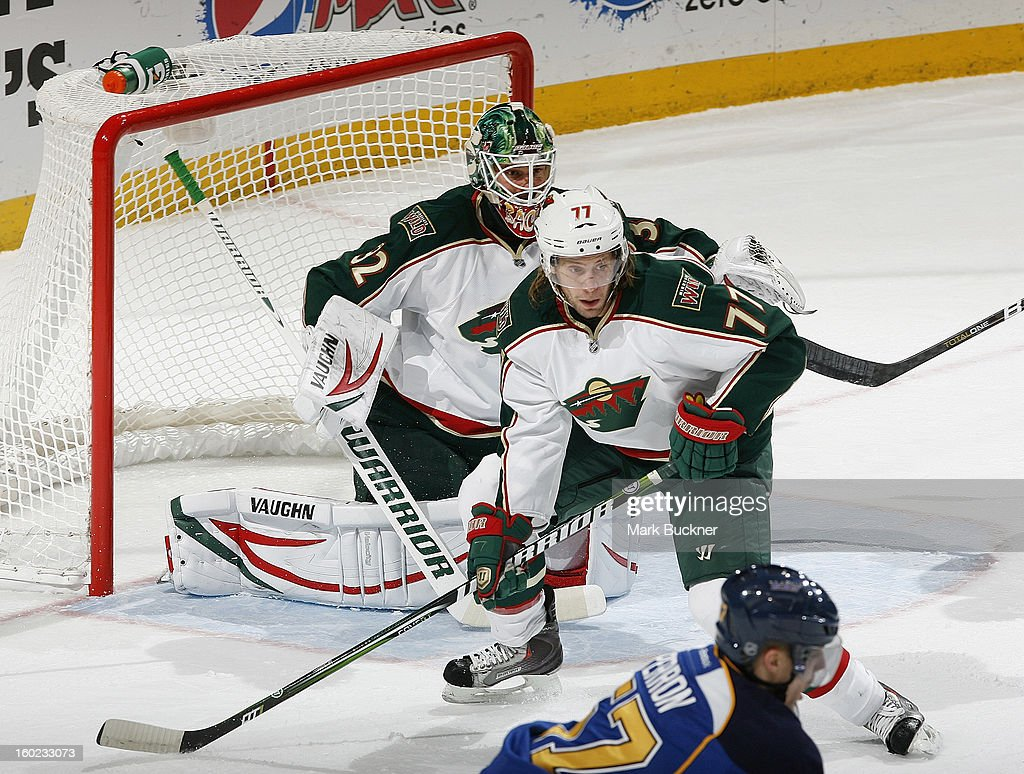 Tom Gilbert #77 and Niklas Backstrom #32 of the Minnesota Wild defend against the St. Louis Blues in an NHL game on January 27, 2013 at Scottrade Center in St. Louis, Missouri.