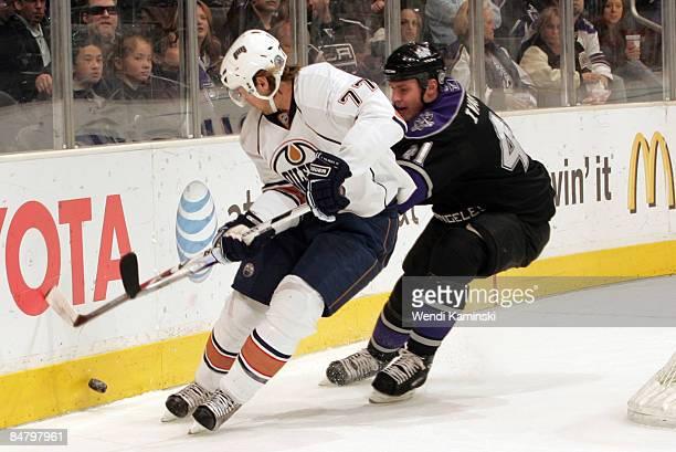 Tom Gilbert of the Edmonton Oilers skates along the boards against Raitis Ivanans of the Los Angeles Kings on February 14 2009 at Staples Center in...