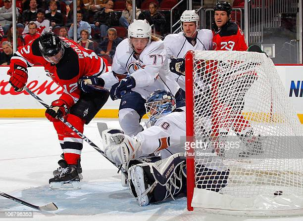 Tom Gilbert of the Edmonton Oilers tries to defend against Brian Rolston of the New Jersey Devils as he shoots the puck past goalie Devan Dubnyk of...