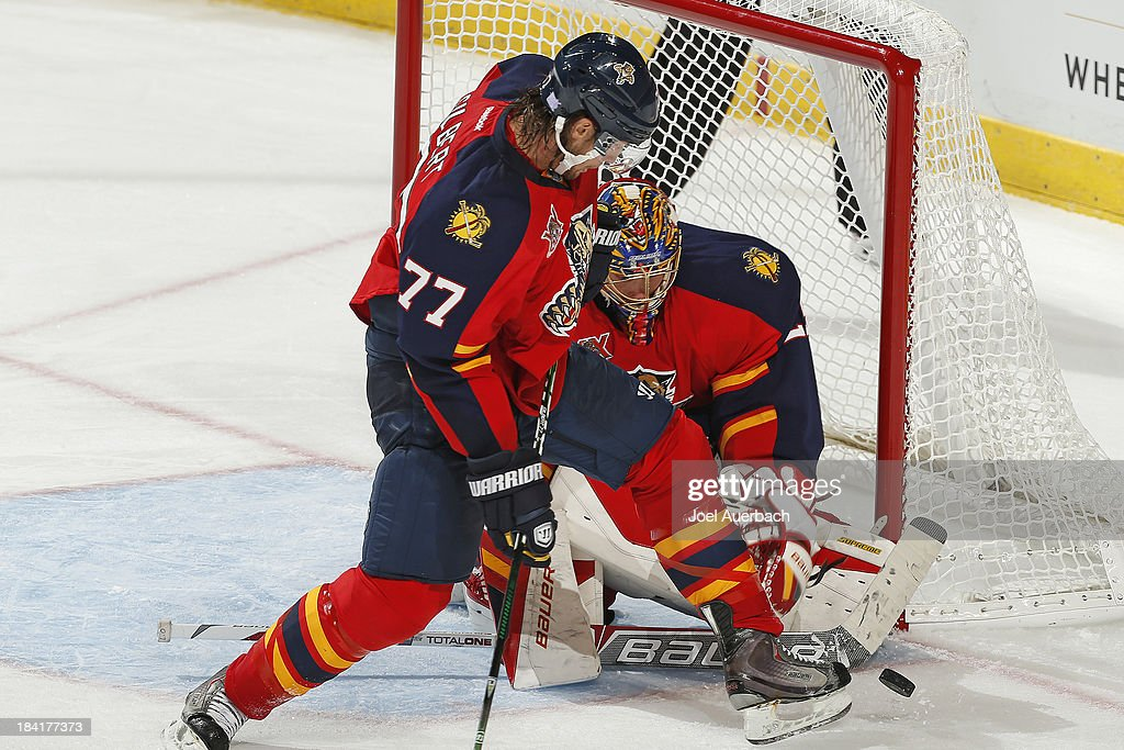 <a gi-track='captionPersonalityLinkClicked' href=/galleries/search?phrase=Tom+Gilbert&family=editorial&specificpeople=687083 ng-click='$event.stopPropagation()'>Tom Gilbert</a> #77 of the Florida Panthers assists defending the net against the Pittsburgh Penguins at the BB&T Center on October 11, 2013 in Sunrise, Florida. The Panthers defeated the Penguins 6-3.
