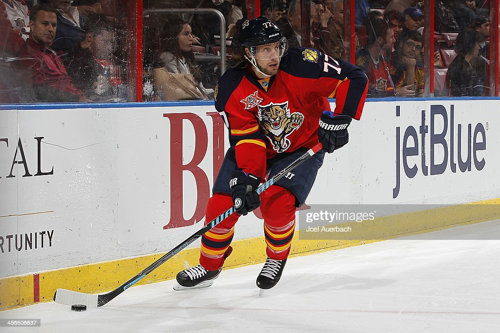 Tom Gilbert of the Florida Panthers circles the net with the puck against the Washington Capitals at the BBT Center on December 13 2013 in Sunrise...