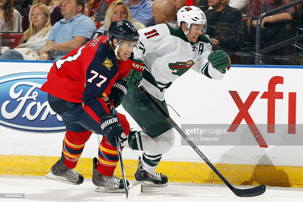 <a gi-track='captionPersonalityLinkClicked' href=/galleries/search?phrase=Tom+Gilbert&family=editorial&specificpeople=687083 ng-click='$event.stopPropagation()'>Tom Gilbert</a> #77 of the Florida Panthers skates for possession against <a gi-track='captionPersonalityLinkClicked' href=/galleries/search?phrase=Zach+Parise&family=editorial&specificpeople=213606 ng-click='$event.stopPropagation()'>Zach Parise</a> #11 the Minnesota Wild at the BB&T Center on October 19, 2013 in Sunrise, Florida.