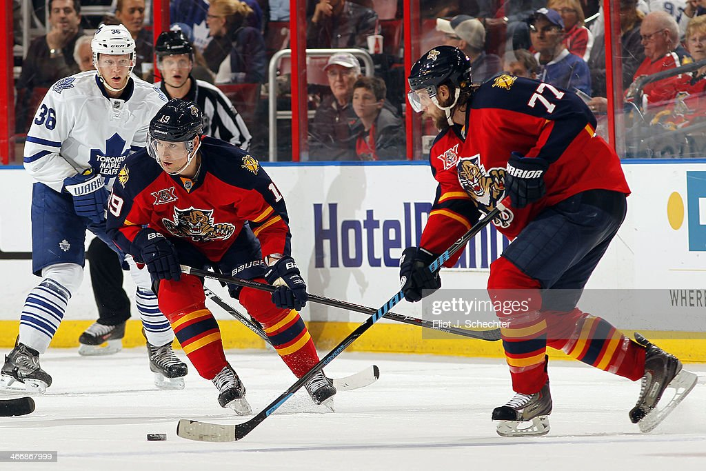 Tom Gilbert #77 of the Florida Panthers skates with the puck along side teammate Scottie Upshall #19 at the BB&T Center on February 4, 2014 in Sunrise, Florida.