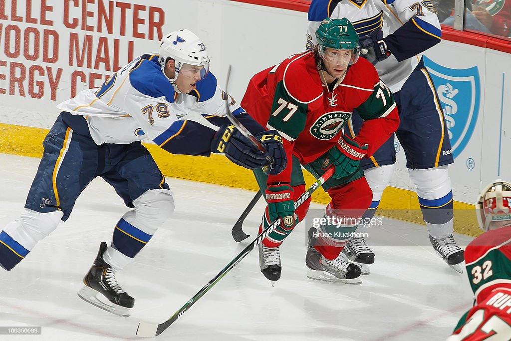 Tom GIlbert #77 of the Minnesota Wild and <a gi-track='captionPersonalityLinkClicked' href=/galleries/search?phrase=Adam+Cracknell&family=editorial&specificpeople=2221797 ng-click='$event.stopPropagation()'>Adam Cracknell</a> #79 of the St. Louis Blues skate to the puck during the game on April 11, 2013 at the Xcel Energy Center in Saint Paul, Minnesota.