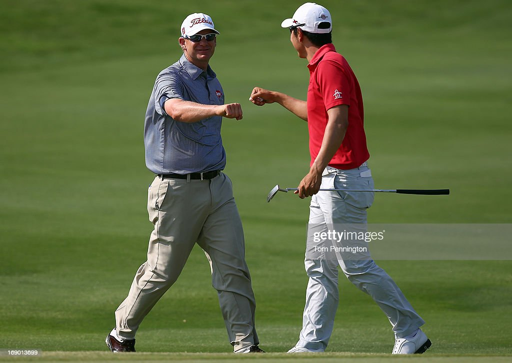 Tom Gillis celebrates with Sang-Moon Bae of South Korea after Gillis chipped in for birdie on the 18th hole during the third round of the 2013 HP Byron Nelson Championship at the TPC Four Seasons Resort on May 18, 2013 in Irving, Texas.