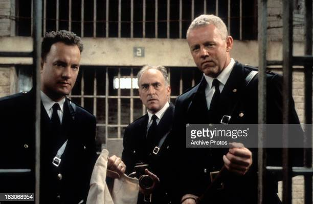 Tom Hanks and David Morse stands outside of a jail cell with two guards in a scene from the film 'The Green Mile' 1999