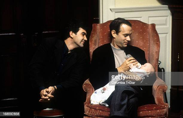Tom Hanks feeds a baby while Antonio Banderas watches in a scene from the film 'Philadelphia' 1994