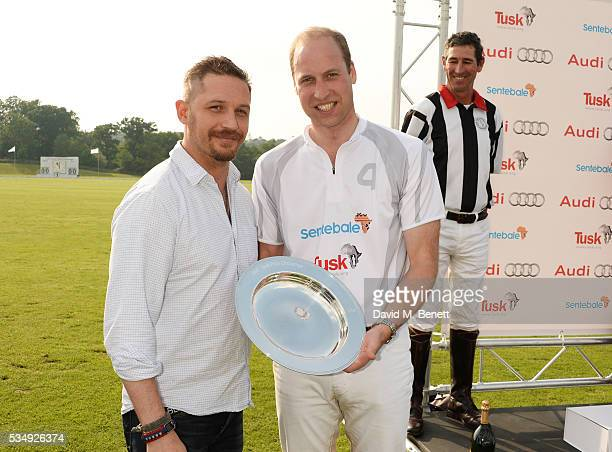 Tom Hardy presents Prince William Duke of Cambridge with a trophy on behalf of Team Audi Ultra during day one of the Audi Polo Challenge at Coworth...