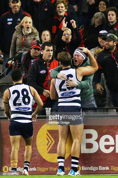 Tom Hawkins of the Cats celebrates his match winning goal with a fan during the round 15 AFL match between the Geelong Cats and the Essendon Bombers...