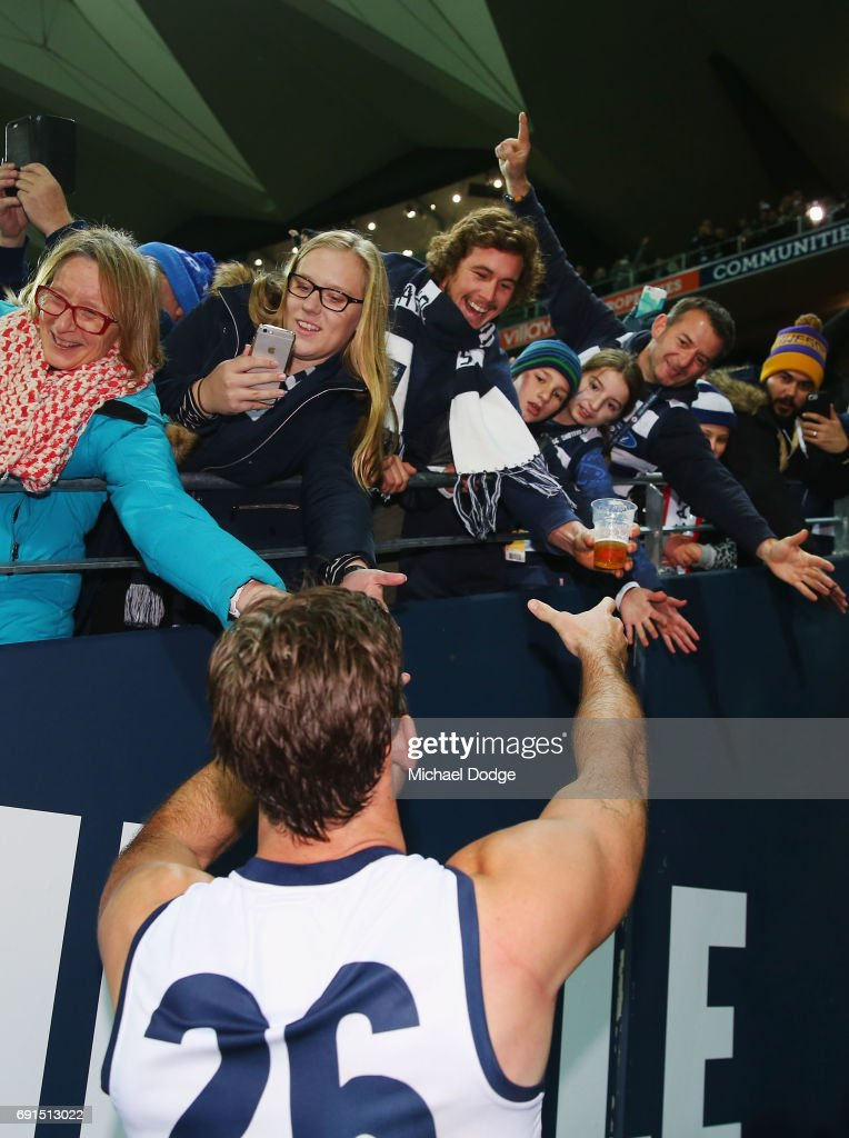 Tom Hawkins of the Cats goes to grab a beer of a fan as he celebrates the win in his 200th match during the round 11 AFL match between the Geelong Cats and the Adelaide Crows at Simonds Stadium on June 2, 2017 in Geelong, Australia.