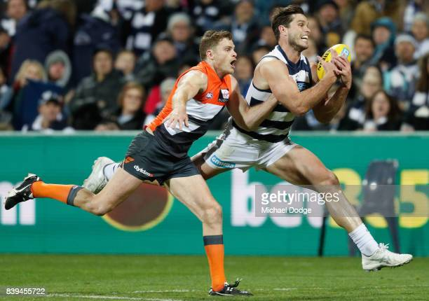 Tom Hawkins of the Cats marks the ball against Heath Shaw of the Giants during the round 23 AFL match between the Geelong Cats and the Greater...