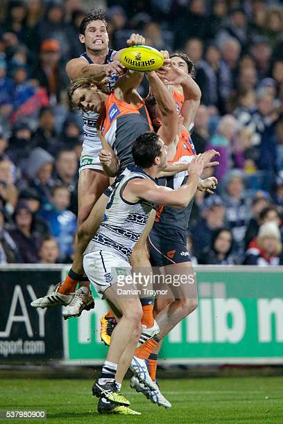 Tom Hawkins of the Cats spoils the ball away from Matt Buntine of the Giants during the round 11 AFL match between the Geelong Cats and the Greater...