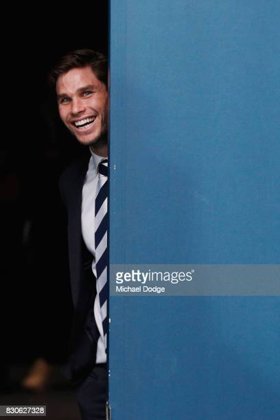Tom Hawkins of the Cats suspended for this week raises a smile after their win as he waits for teammates to come off the ground during the round 21...