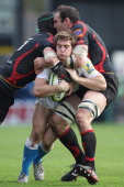 Tom Heathcote of Bath is sandwiched between Scott Morgan and Robert Sidoli of Newport Gwent Dragons during the LV Cup match at Rodney Parade on...