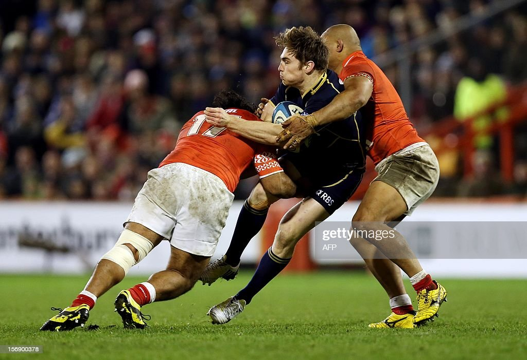 Tom Heathcote (C) of Scotland evades a tackle during the International rugby union test match between Scotland and Tonga at Pittodrie in Aberdeen on November 24, 2012. Tonga beat Scotland 21-15.