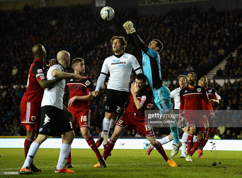 Tom Heaton of Bristol City punches clear from Chris Martin of Derby County during the npower Championship match between Derby County and Bristol City at Pride Park Stadium on March 29, 2013 in Derby, England.