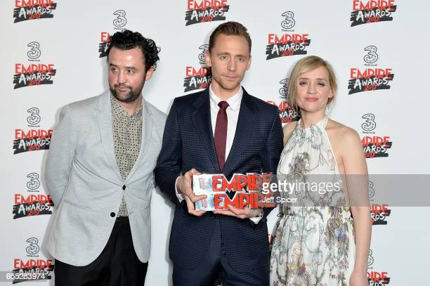 Tom Hiddleston poses in the winners room with his two awards for Empire Hero and Best TV Series for The Night Manager with presenters AnneMarie Duff...