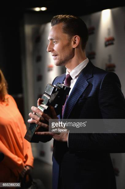 Tom Hiddleston poses in the winners room with his two awards for Empire Hero and Best TV Series for The Night Manager at the THREE Empire awards at...