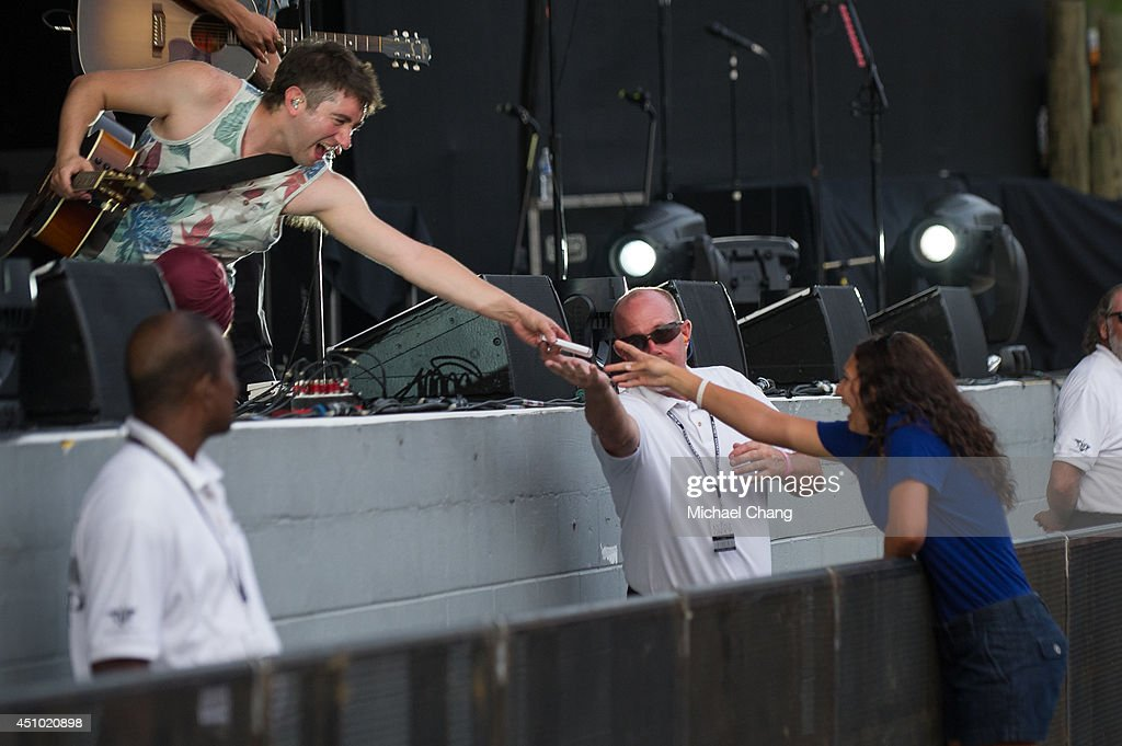 Tom Higgenson of the Plain White T's hands a cell phone back to a fan during their performance at The Amphitheater at the Wharf on June 21, 2014 in Orange Beach, Alabama.