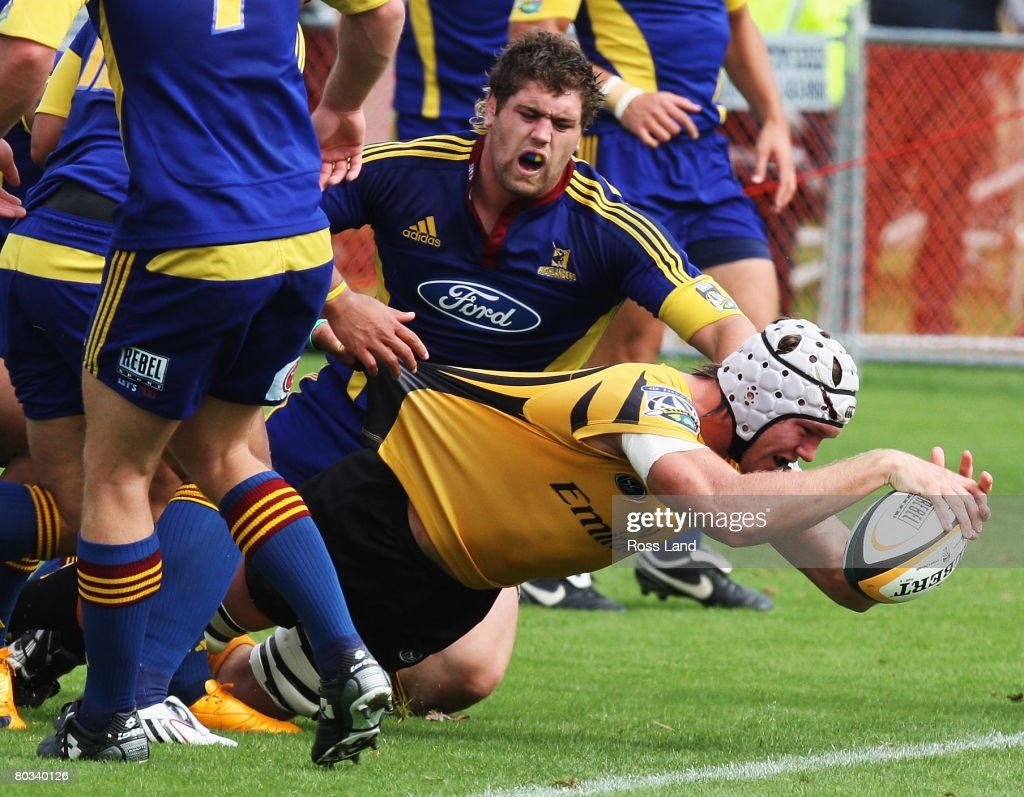 Tom Hockings of the Western Force dives through the tackle of Tom Donnelly of the Highlanders to score a try during the round six Super 14 match...