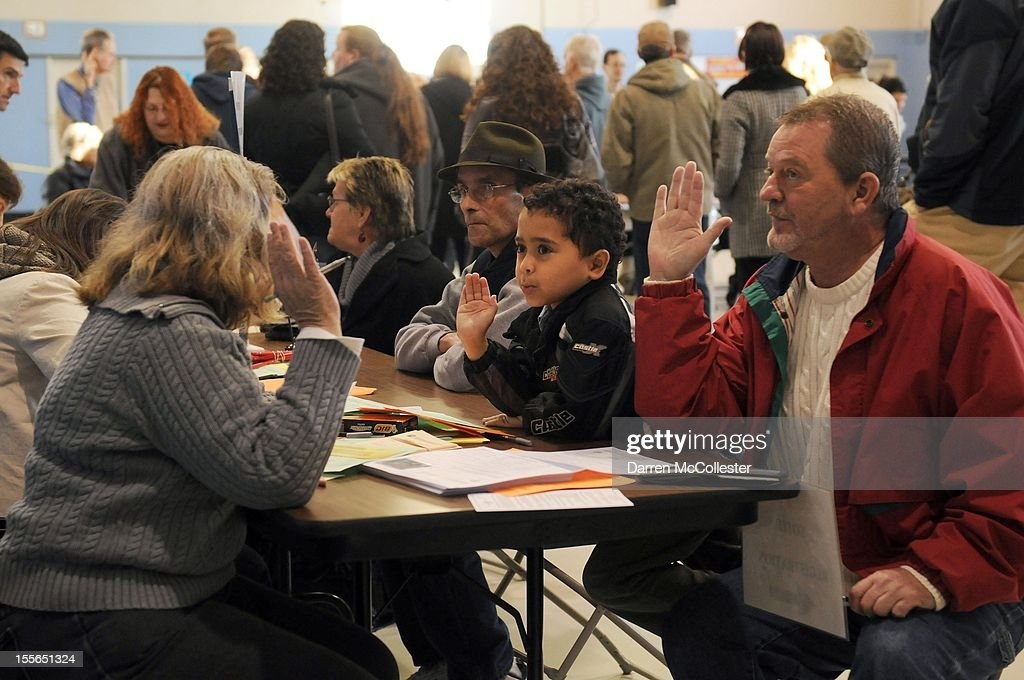 Tom Hoisington (R) raises his right hand along with grandson Tonykus Hebert, 6, after being registered to vote at the Bishop Leo O'Neil Youth Center on November 6, 2012 in Manchester, New Hampshire. The swing state of New Hampshire is recognised to be a hotly contested battleground that offers 4 electoral votes, as recent polls predict that the race between U.S. President Barack Obama and Republican presidential candidate Mitt Romney remains tight.