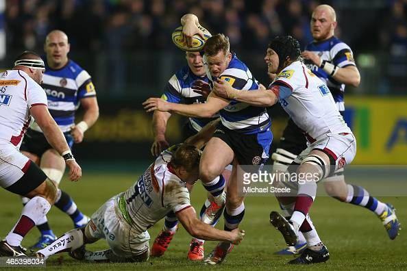 Tom Homer of Bath is held up by David Seymour and Magnus Lund of Sale during the Aviva Premiership match between Bath Rugby and Sale at the...