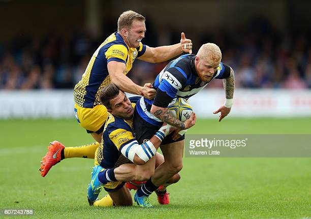 Tom Homer of Bath Rugby is tackled by Perry Humphreys and Wynand Olivier of Worcester Warriors during the Aviva Premiership match between Bath Rugby...