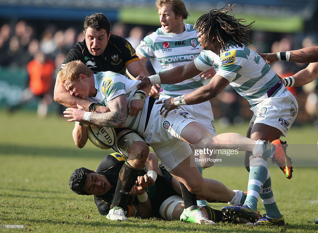 Tom Homer of London Irish is tackled by George Pisi and Phil Dowson during the Aviva Premiership match between Northampton Saints and London Irish at...