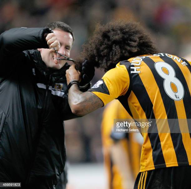 Tom Huddlestone of Hull city celebrates after scoring the team's 4th goal by having his hair cut after vowing to not have his hair cut until he...