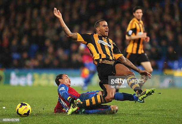 Tom Huddlestone of Hull City grimaces as he is tackled by Marouane Chamakh of Crystal Palace during the Barclays Premier League match between Crystal...