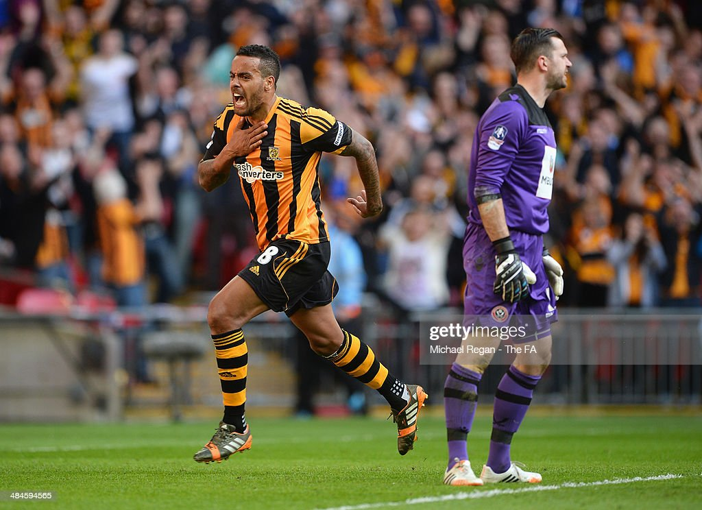 Tom Huddlestone (R) of Hull City runs past goalkeeper Mark Howard of Sheffield United as he celebrates scoring their third goal during the FA Cup Semi-Final match between Hull City and Sheffield United at Wembley Stadium on April 13, 2014 in London, England.