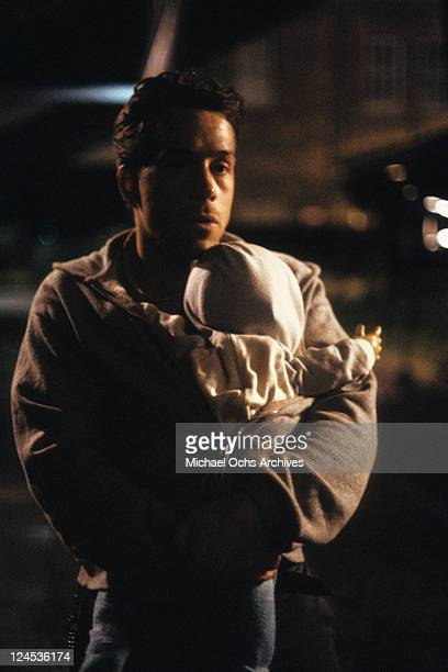 Tom Hulce holding baby in a scene from the film 'Dominick And Eugene' 1988