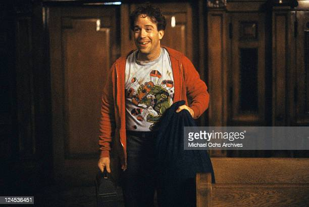 Tom Hulce holding lunch box and bag in a scene from the film 'Dominick And Eugene' 1988