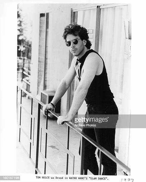 Tom Hulce leaning against rail in a scene from the film 'Slam Dance' 1987