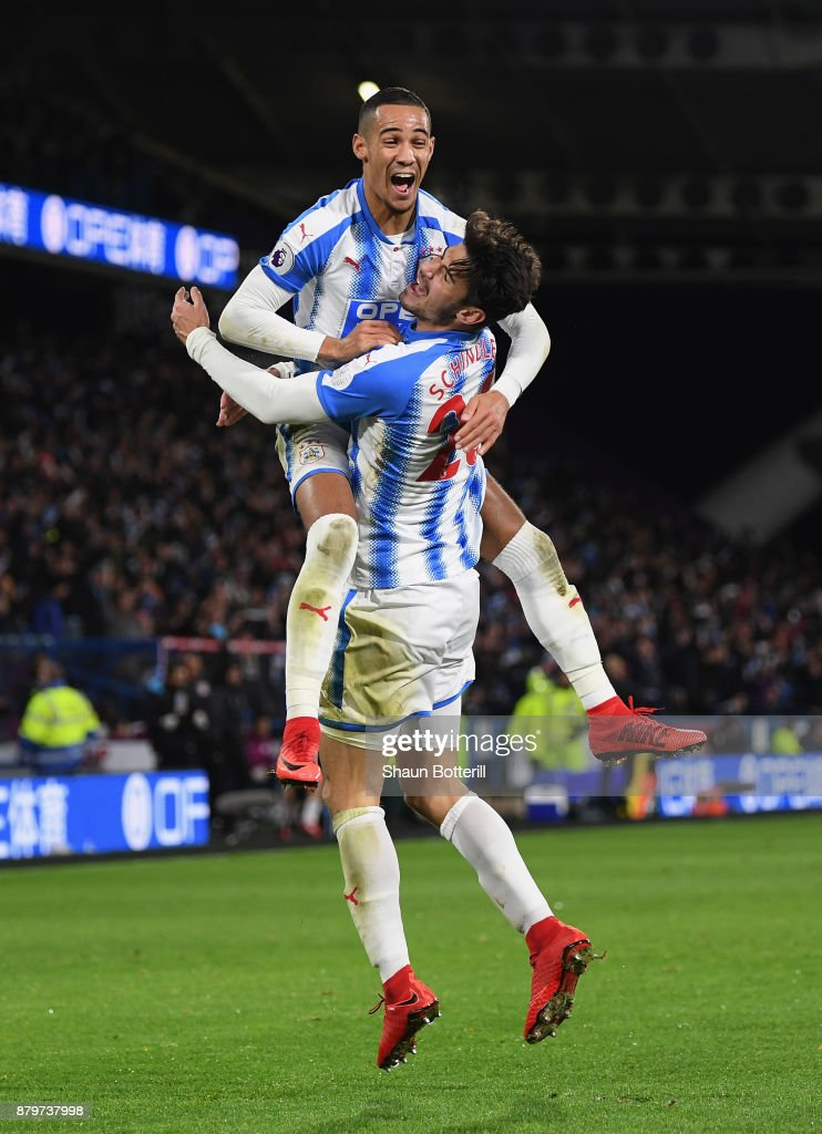 Tom Ince and Christopher Schindler of Huddersfield Town celebrate after Nicolas Otamendi of Manchester City scored the an own goal during the Premier League match between Huddersfield Town and Manchester City at John Smith's Stadium on November 26, 2017 in Huddersfield, England.