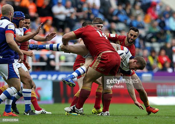 Tom Johnstone of Wakefield Wildcats tackled by Dave Taylor and Eloi Pelissier of Catalans Dragons during the First Utility Super League match between...