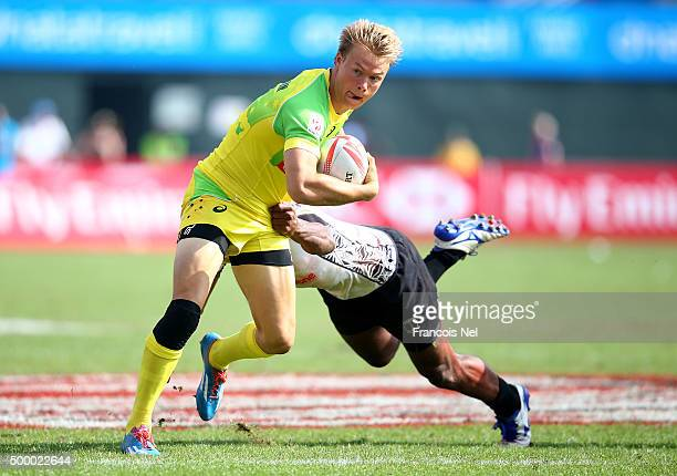 Tom Kingston of Australia is tackled by Isake Katonibau of Fiji during the Emirates Dubai Rugby Sevens HSBC World Rugby Sevens Series Cup Quarter...