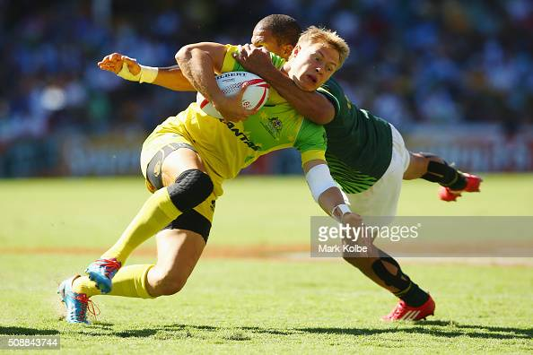 Tom Kingston of Australia is tackled high by Juan de Jongh of South Africa during the 2016 Sydney Sevens cup semi final match between Australia and...