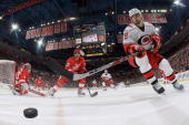 Tom Kostopoulos of the Carolina Hurricanes reaches for the puck defended by Patrick Eaves of the Detroit Red Wings as goalie Jimmy Howard watches the...